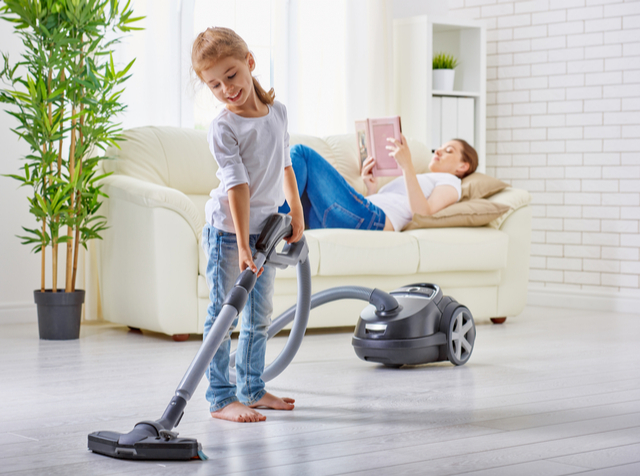 Child vacuuming the floor